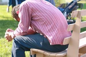 Man praying on park bench