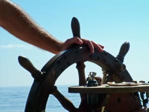 sailor on pleasure boat at wheel of boat