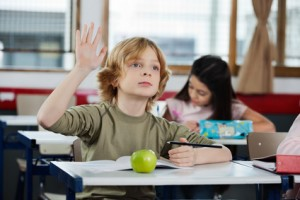 Schoolboy Looking Away While Raising Hand At Desk