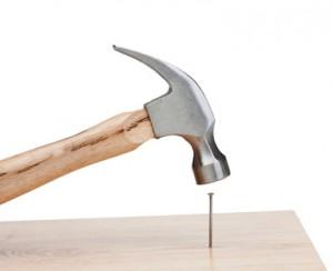 Hammer hitting a nail into a wood